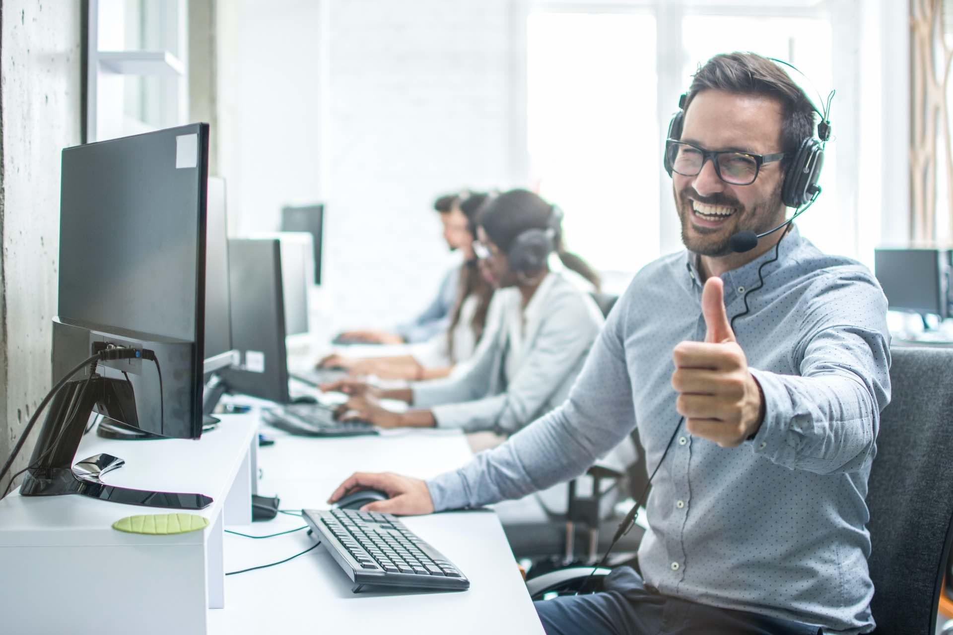 BPO agent by his desk giving the thumbs up