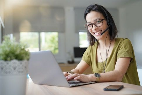 Call center female agent with headset by laptop working from home