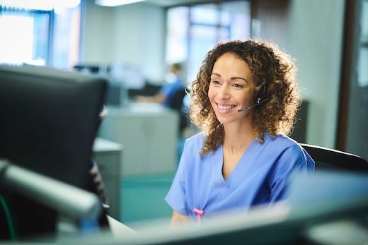 Smiling girl with curly hair answering calls in healthcare verticals environment with hospital clothes and headset