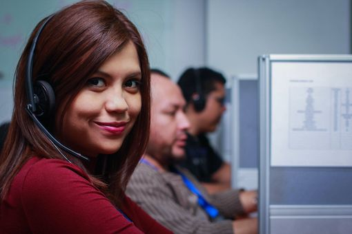 SkyCom Call Center agent with red jumper and headset smiling into camera