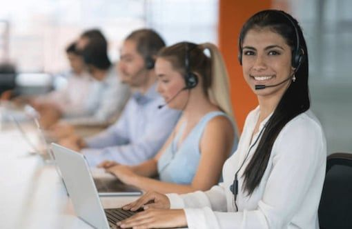 BPO female agent sitting by desk smiling with colleagues