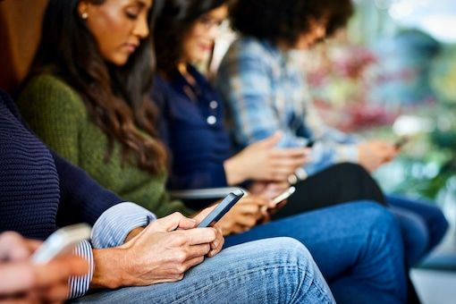 Young people with mobile phones in waiting room
